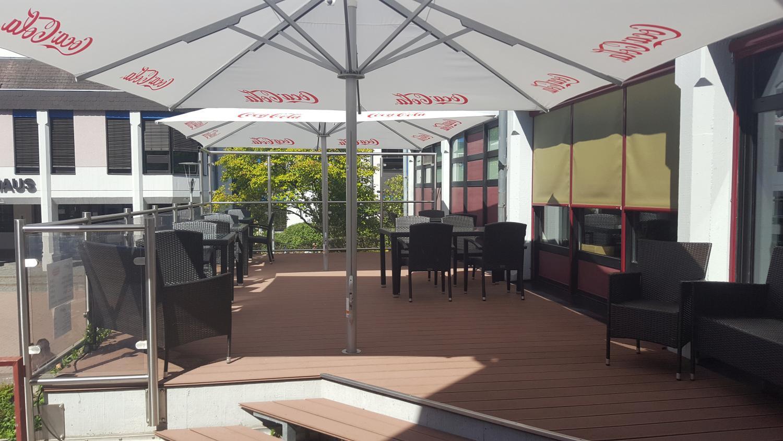 Ein Teil des Außenbereichs vom Restaurant Die Bühne in Ramstein. Bestuhlung und Sonnenschutz