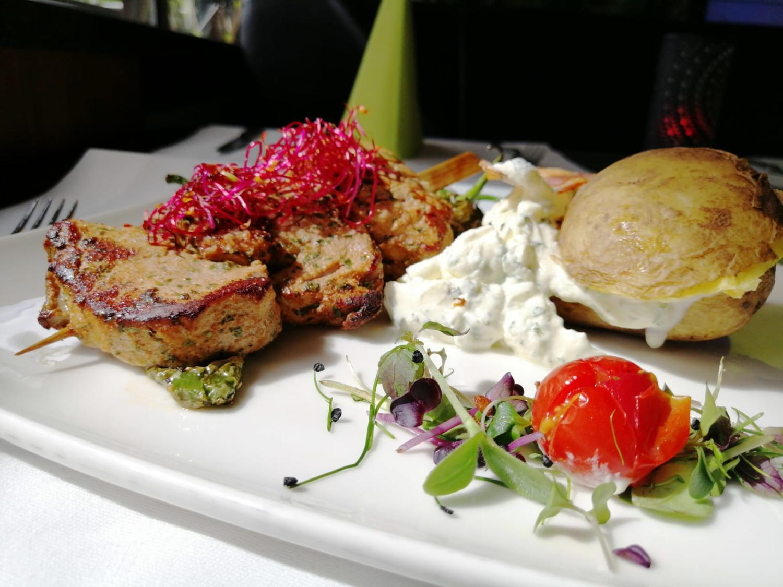 Fleischspieß mit Ofenkartoffel, Sour Cream und Dekor auf einem Teller angerichtet